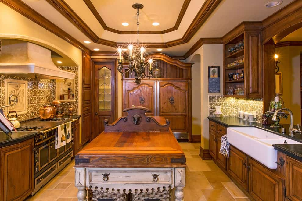 Warm kitchen showcases a rustic island bar flanked by wooden cabinets and an arched cooking alcove. It is illuminated by a candle chandelier and recessed lights mounted on the tray ceiling.