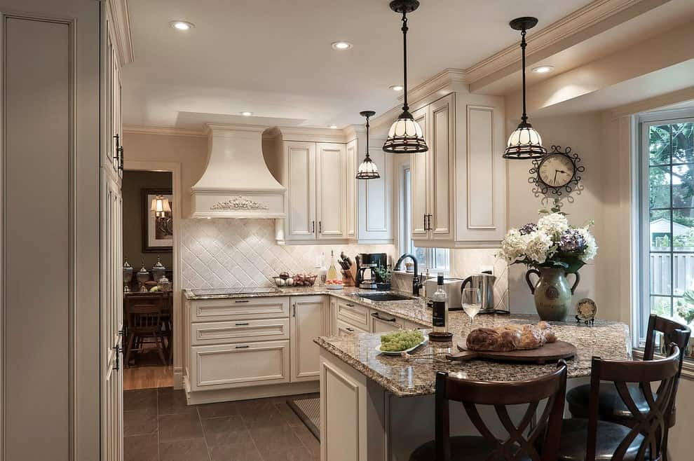 Victorian kitchen with white cabinetry and a peninsula paired with dark wood chairs. It includes granite countertops and lovely dome pendants that hung from a regular ceiling.