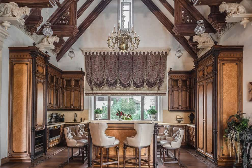 A grand candle chandelier hangs over the central island surrounded by tufted wingback chairs. This kitchen has hardwood flooring and a cathedral ceiling lined with dark wood beams.