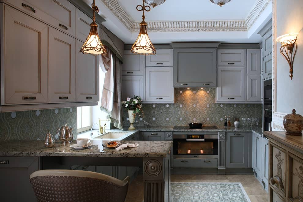 A round back counter chair sits at a granite top peninsula lighted by glass dome pendants. There are gray lower cabinets and white upper cabinets against the green patterned backsplash.