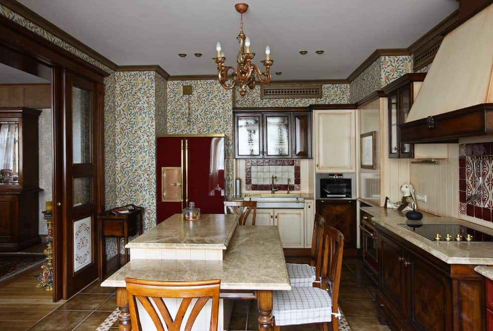 This kitchen is clad in floral wallpaper and beige backsplash accented with red-bordered tiles. It has wooden cabinets and a raised breakfast island with plaid cushioned chairs illuminated by a classic chandelier.
