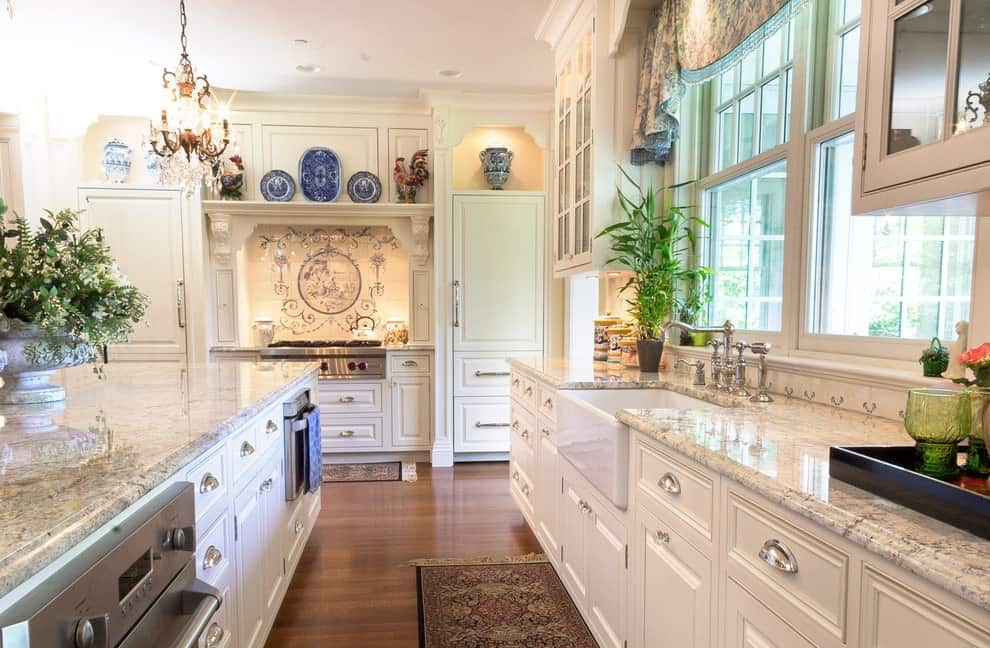 Ceramic plates and vases add a gorgeous accent to the white cabinets in this kitchen with glazed windows and hardwood flooring topped by a classic tasseled rug. It includes granite countertops and a farmhouse sink paired with chrome fixtures.