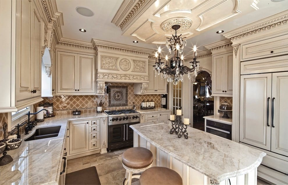 A fancy chandelier hangs over the marble top center island that's paired with round cushioned stools. It is surrounded by white cabinetry and an alcove hood with intricate design.