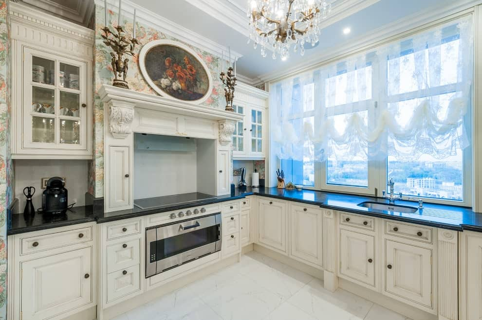 A bright kitchen boasts white lower cabinets and glass front upper cabinets flanking an alcove hood that's clad in floral wallpaper. It has marble tiled flooring and glass-paneled windows dressed in lace roman shades.