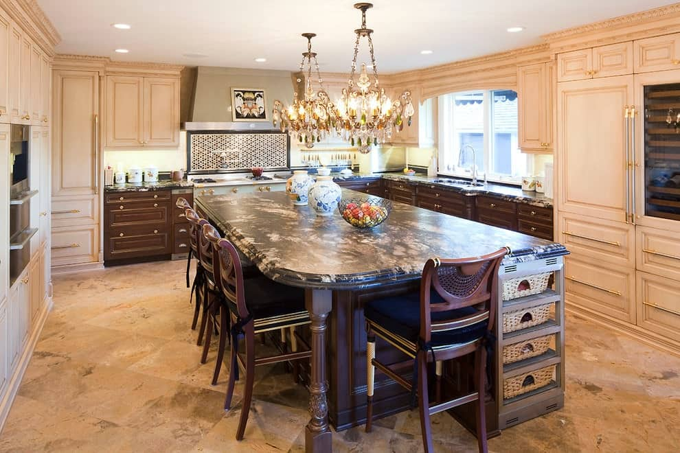 Fabulous kitchen features a large granite top island with wooden counter chairs surrounded by beige and wooden cabinetry. It is illuminated by a pair of glamorous crystal chandeliers and recessed ceiling lights.