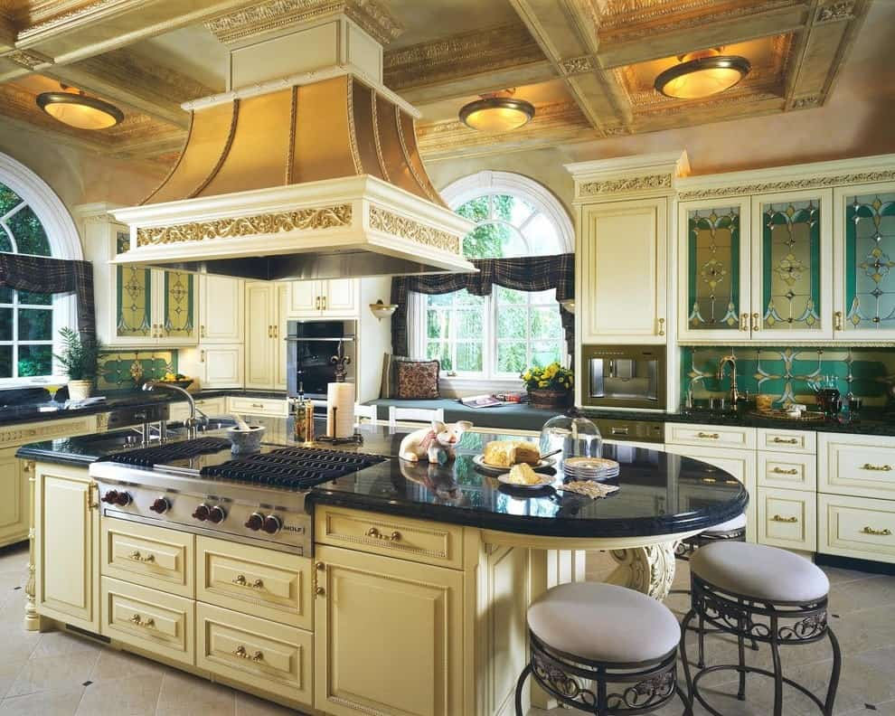 Upper cabinets with stained glass doors complement the green decorative backsplash tiles fixed above black granite countertops. This kitchen has a central island under the ornate vent hood illuminated by semi-flush lights mounted on the coffered ceiling.