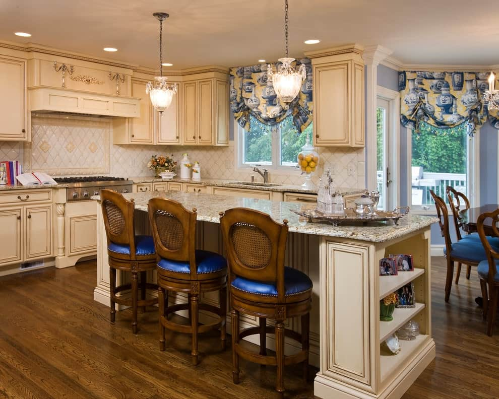 Victorian kitchen with rich hardwood flooring and glazed windows covered in vase printed roman shades. It includes beige cabinetry and a granite top island with round counter chairs fitted with blue cushions.