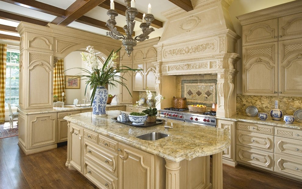 Classic kitchen showcases ornate cabinetry and a light wood island bar lighted by a vintage chandelier that hung from the wood beam ceiling. It includes granite countertops and a stainless steel range hood accented by bordered backsplash tiles.