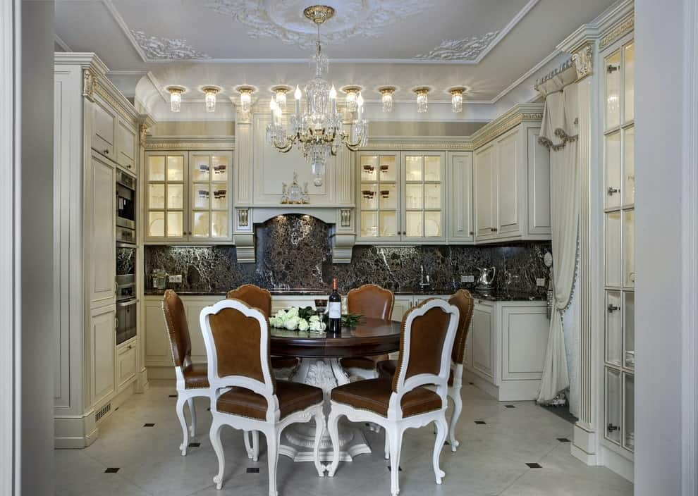 A glass candle chandelier that hung from the ornate ceiling illuminates the round dining set over tiled flooring. This eat-in kitchen offers stainless steel appliances and white cabinetry contrasted by a black backsplash.