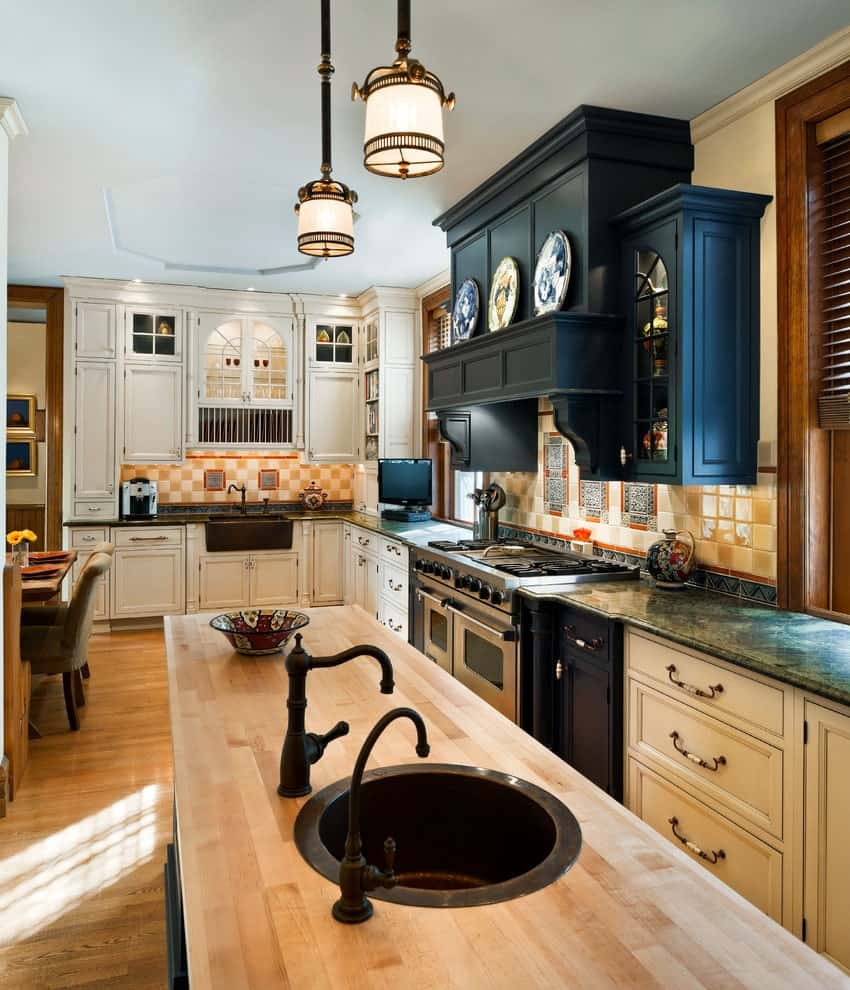 An open kitchen with contrasting white cabinetry and a black range hood designed with decorative plates. It includes checkered backsplash tiles and an island bar with a wooden countertop and round sink paired with wrought iron faucets.