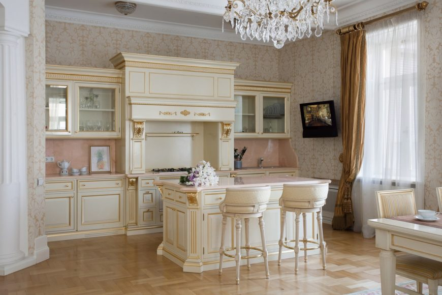 Clad in classy patterned wallpaper, this kitchen boasts cream cabinetry and a matching breakfast island with gold trims. It has light hardwood flooring and a glazed window covered in white sheer curtain and elegant brown drapery.