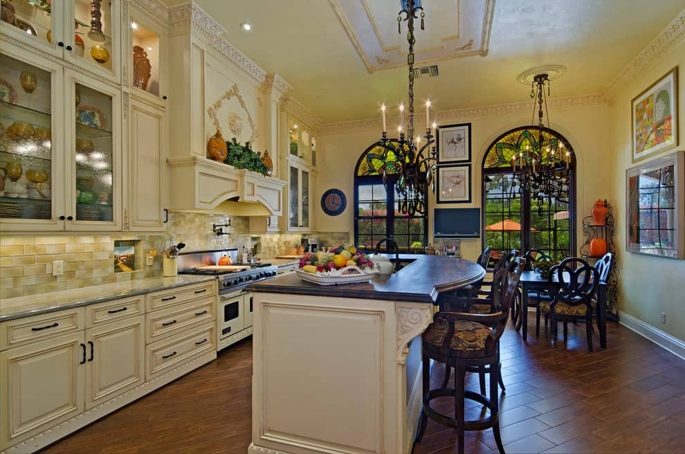 An eat-in kitchen decorated with framed artworks that are mounted on the beige walls lined with ornate crown molding. It has a dark wood dining set and a white breakfast island lighted by candle chandeliers.
