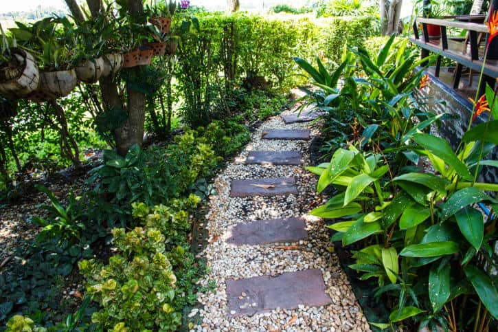 Wide pebble bed supports rectangular flagstone pieces in this garden walkway.