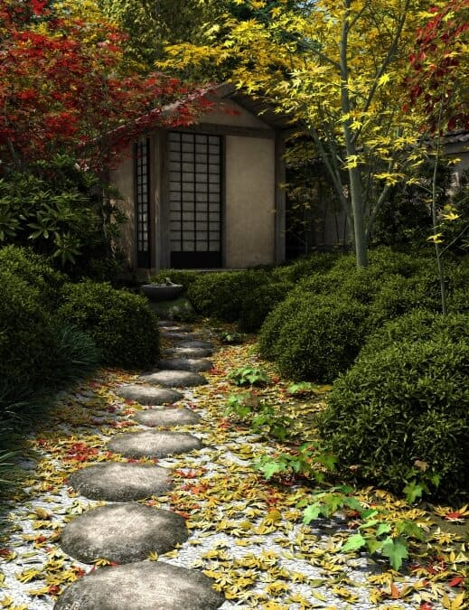 Circular stone pieces define this walkway, strewn with Japanese maple leaves.