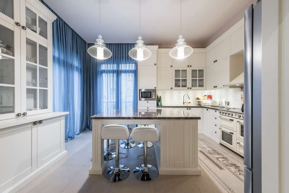 Clean white kitchen with breakfast island, stylish pendant lighting, and tiled marble countertops.