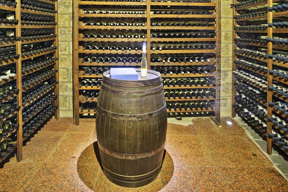 Built-in wood wine rack on a brick wall with barrel table at the center