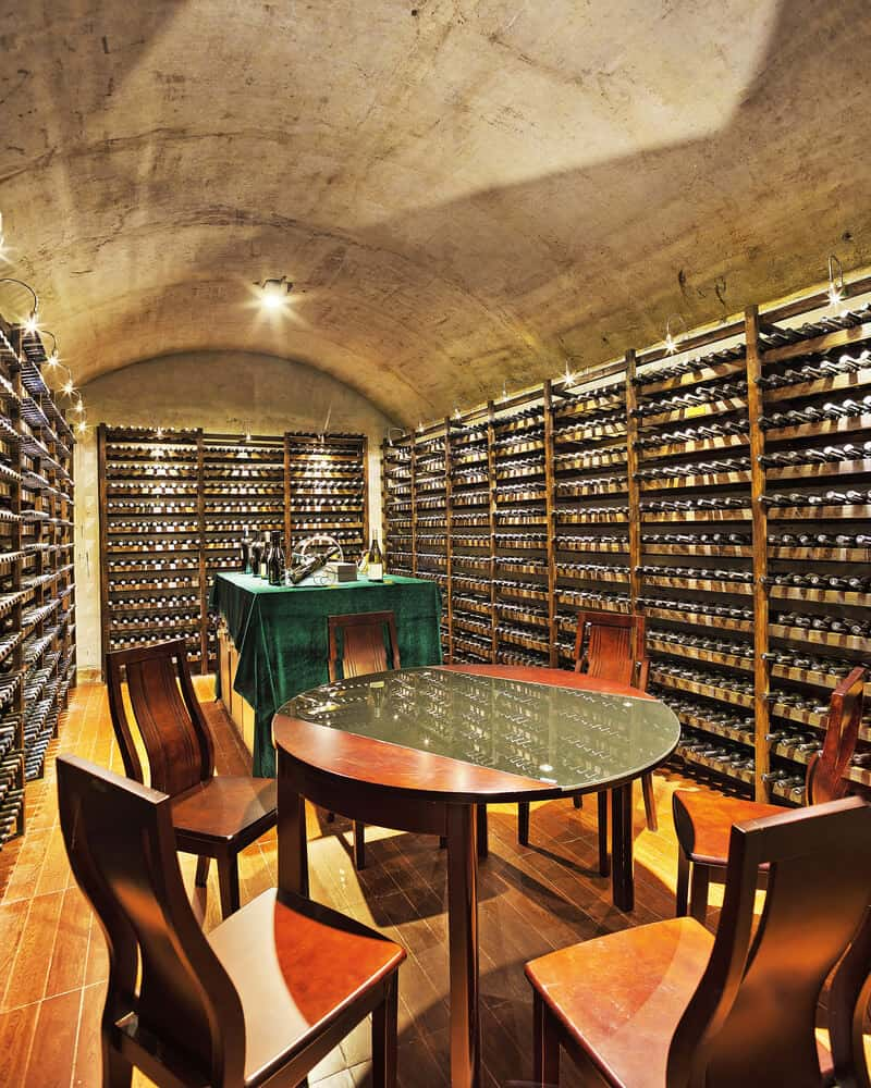 Rustic wine cellar with concrete arched ceiling and hardwood flooring along with two tasting areas.