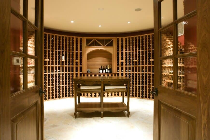 Large round wooden design wine cellar with tasting table. Walls are in brick and liquor cabinets are made of wood.