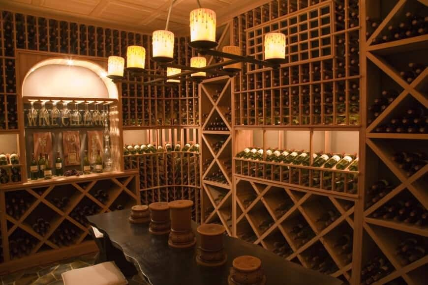 Extensive bottle storage capability in this custom wine room with a long table and benches for an included wine sampling area. The room is lighted by a lovely rustic candle chandelier.