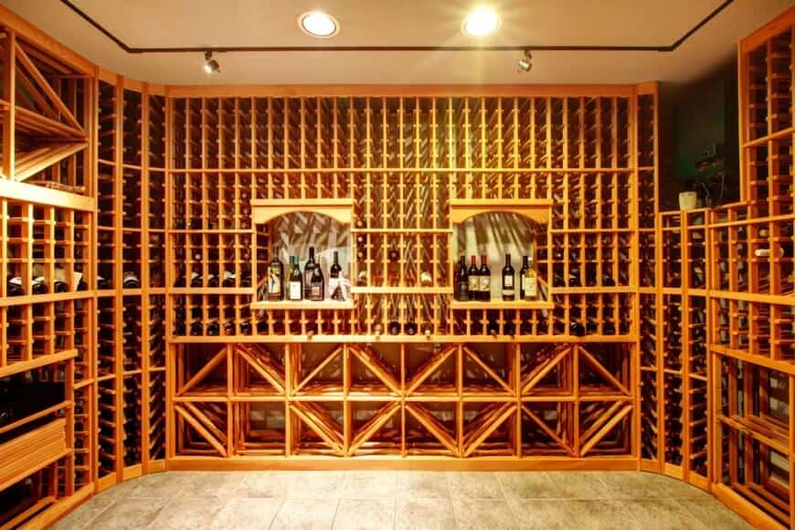 Floor-to-ceiling light wood cabinets in a dedicated wine room over a tiled flooring.