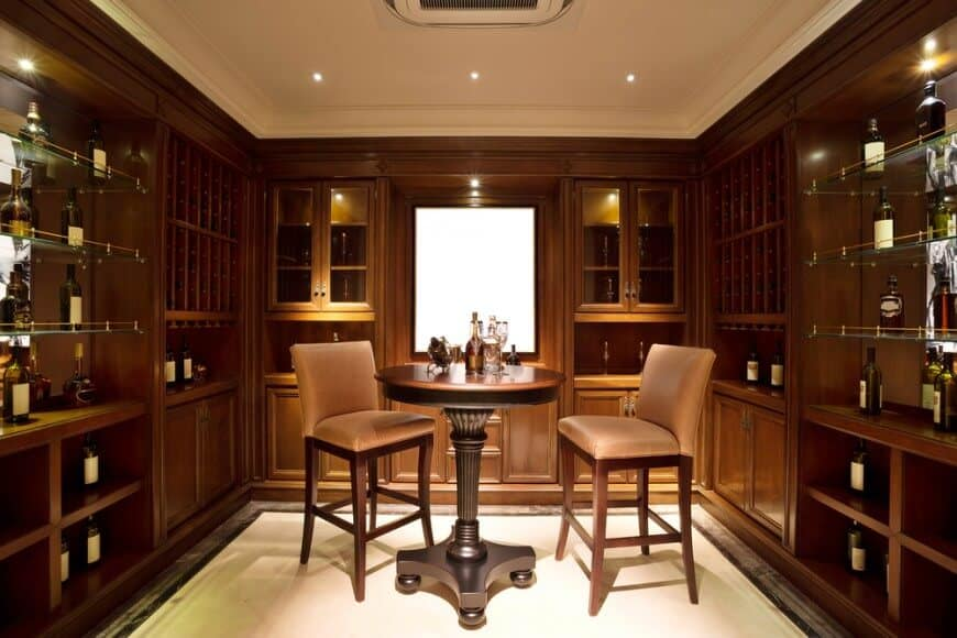 A luxurious wine cellar surrounded by handcrafted storage cabinets features an LCD display panel and an intimate table for two.
