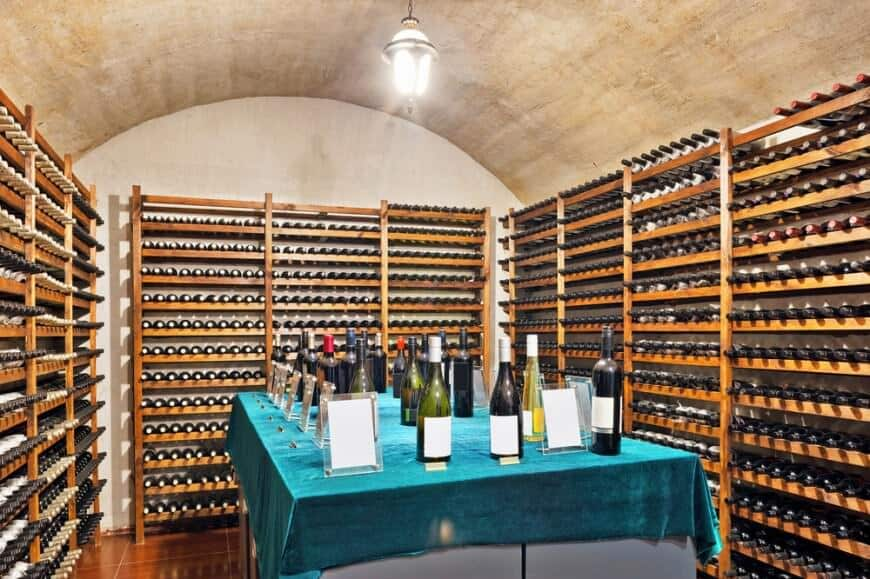 Simple wine cellar with universal storing racks throughout and elevated tasting table in the center topped with velvet blue green cloth. This is a simple design that you could implement in any spare part of your basement.