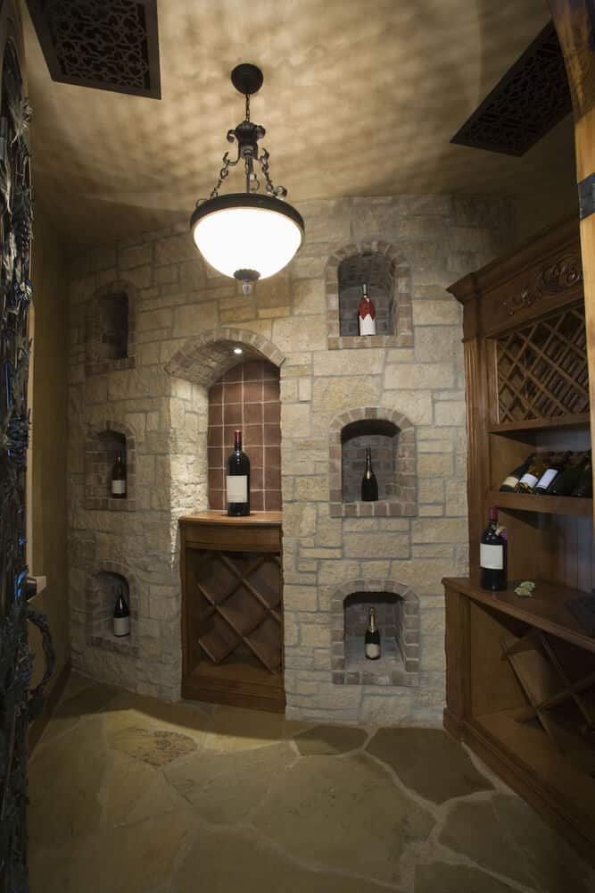 Example of an effective brick wall design that incorporates bottle storage for a basement or home bar area. This room is complemented with a built-in wood liquor cabinet.