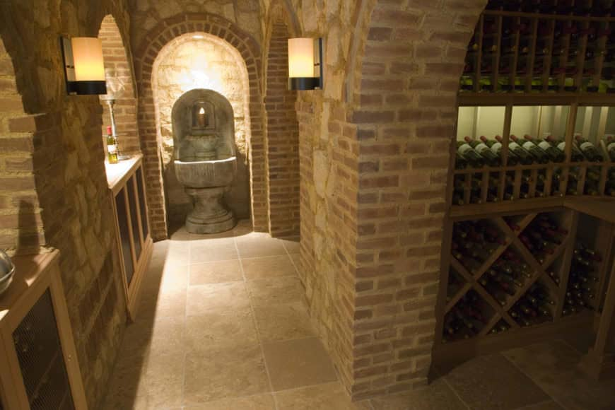 A sophisticated wine cellar surrounded with bricks and has built-in wood wine shelves. It has a mini hallway lighted by lovely wall sconces and leads to a concrete pedestal.