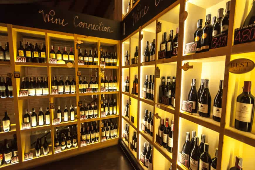 Well-organized wine storage with wooden shelves that are sorted by type and by year.