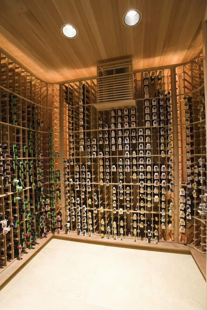 Spectacular wine cellar with a floor to ceiling wine rack that allows thousands of bottles to be stored. It has a wooden ceiling with lights that complement the wine rack along with tiled flooring.