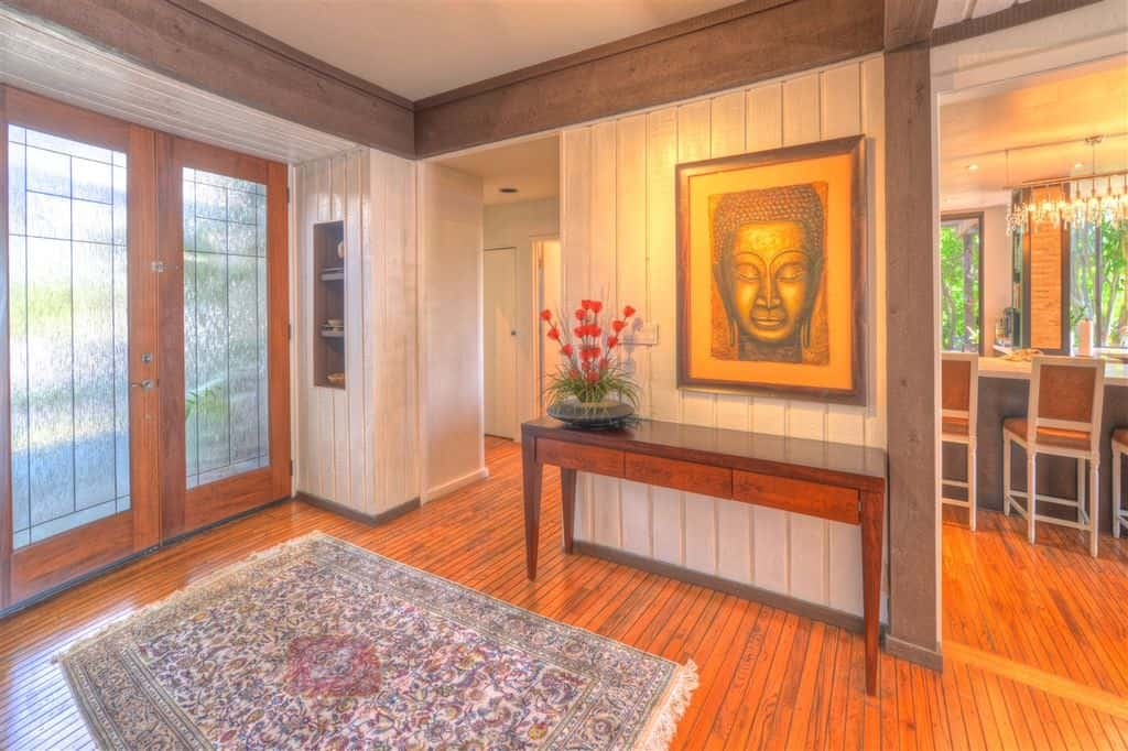 Asian foyer with glass double front doors, shiplap wall panels, built-in shelving and a console table.