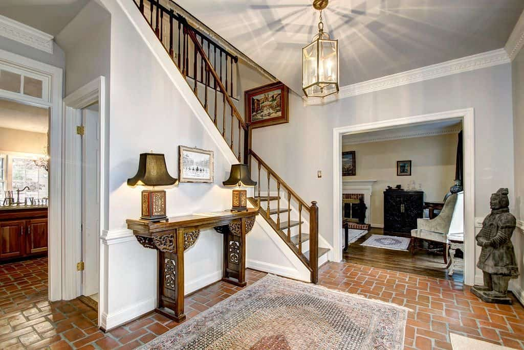 Classy foyer featuring brick tiles flooring topped by a rug, along with gray walls and a pendant lighting. There's a statue on the corner decorating the home.