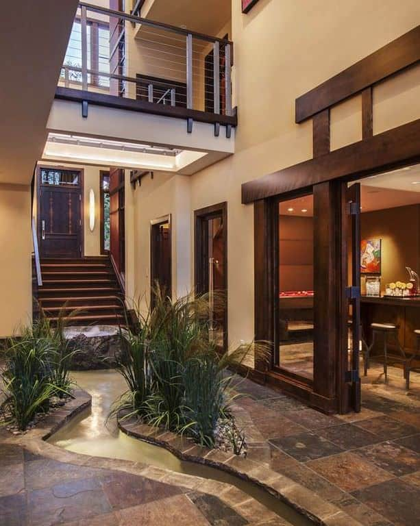 Large Asian foyer with beige walls and a straight staircase leading to an indoor Zen garden.