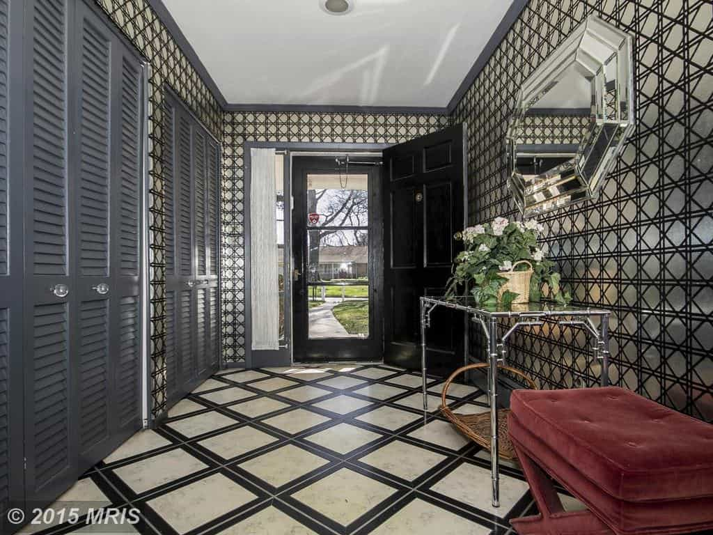 Black foyer boasts patterned walls that complement the tiled flooring. It includes gray storage closets opposite the matching mirror and console table.