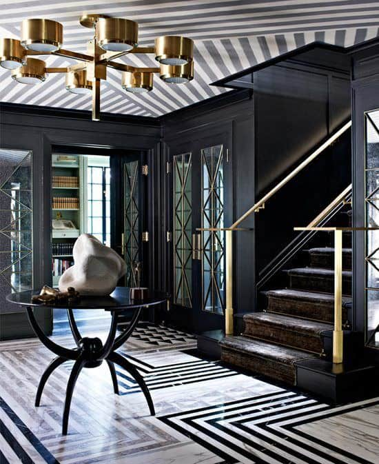 A striking black foyer lighted with a copper chandelier that hung from a striped ceiling over a round center table with spider-like legs. It includes a wooden staircase along with complex marble tile flooring.