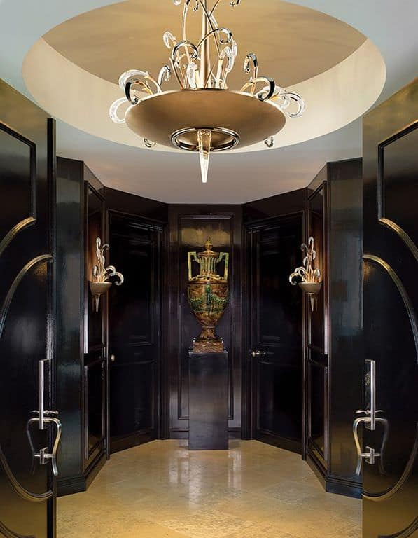 Luxurious foyer illuminated by a glass chandelier that hung from a dome tray ceiling. Matching sconces are mounted on rich dark wood walls along with a sculpture that sits on a pedestal.