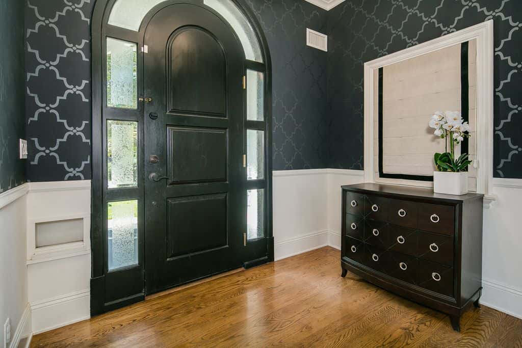 This foyer showcases a half patterned black wall above white wainscoting. It has a black arched door surrounded with glass panels adjacent to the wooden console table beneath a white mirror.