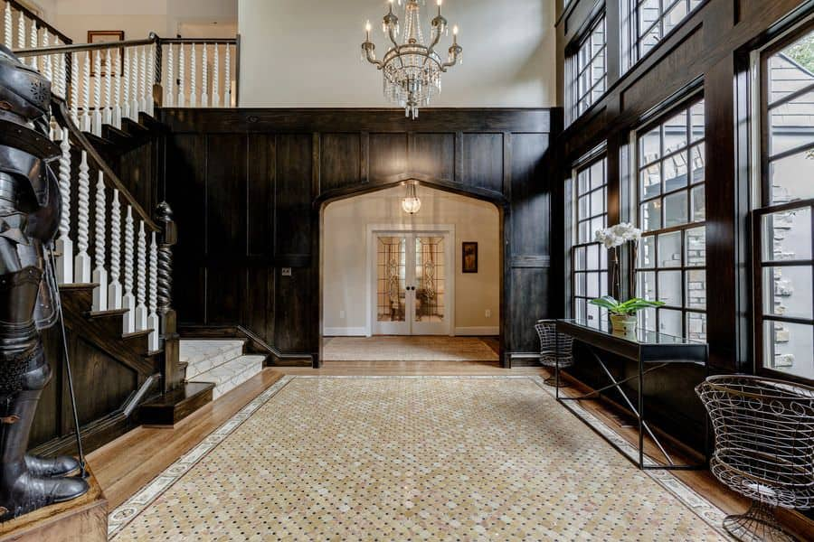This elegant foyer features a hardwood flooring topped by a rug, black walls with white detail and a grand chandelier lighting the area. The glass windows let the sunlight through.