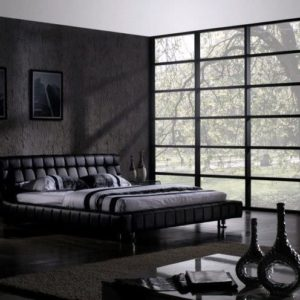Contemporary black primary bedroom with full-length windows. low platform bed and dark hardwood flooring.