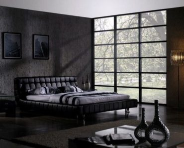 Contemporary black master bedroom with full-length windows. low platform bed and dark hardwood flooring.