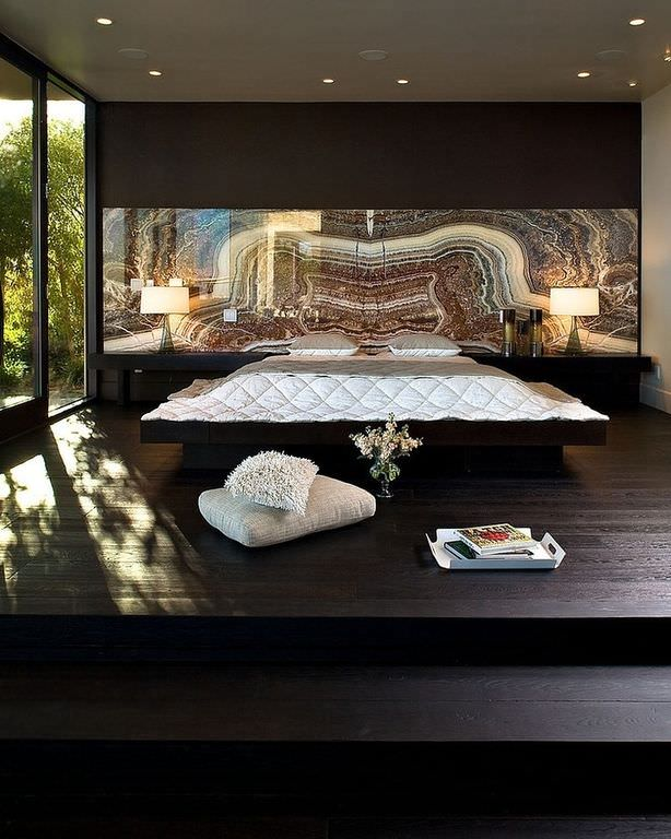 This primary bedroom boasts a huge art piece behind the platform bed. It includes dark hardwood flooring and glass windows along with recessed lighting.