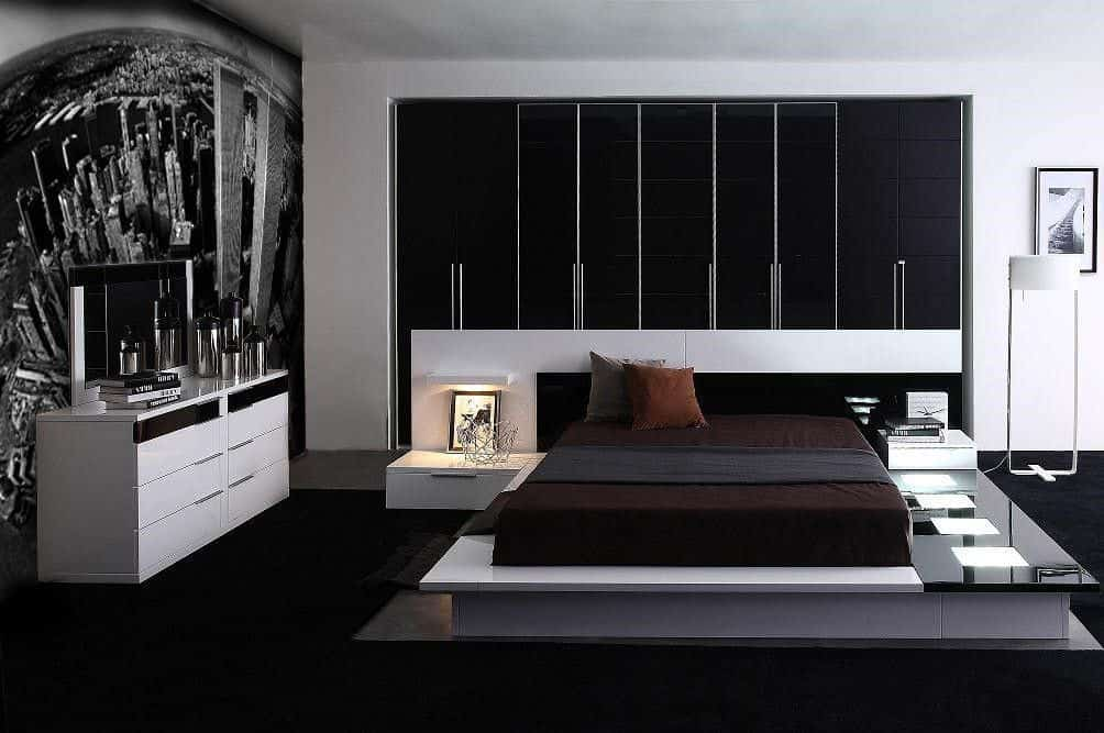Contemporary black primary bedroom featuring an elevated platform bed with a custom oversized headboard and white vanity on its side.