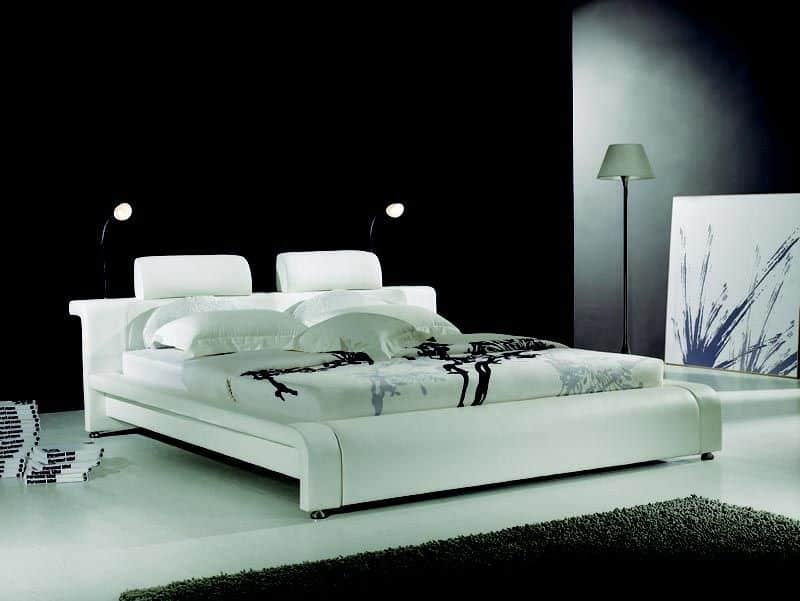 Black and white primary bedroom features a modern bed lighted by desk lamps and a floor lamp over concrete flooring.