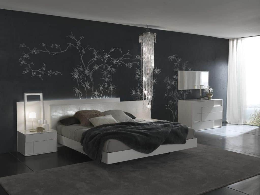 The crystal chandelier, white bed and tables appear to float against the black accent wall and tile flooring.