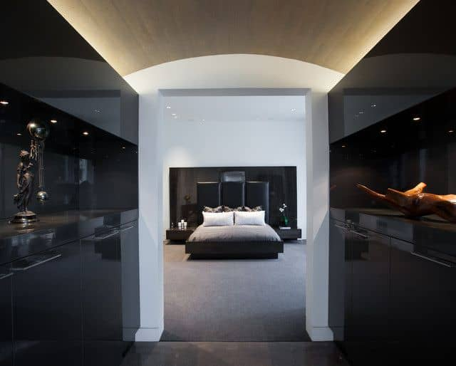 This Modern Black Master Bedroom Has Carpet Flooring And A Doorless Entry Flanked By Sculptural Displays