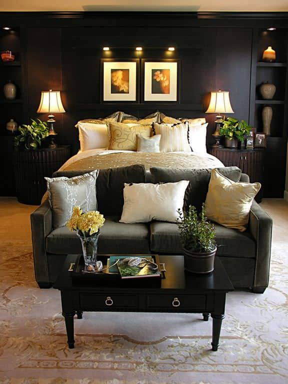 Traditional black primary bedroom with built-in shelving, indoor plants and a sofa and coffee table at the foot of the bed.