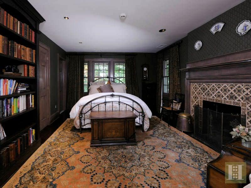 Traditional master bedroom with black interior wallpaper, built-in bookshelf, a fireplace and carpet flooring.