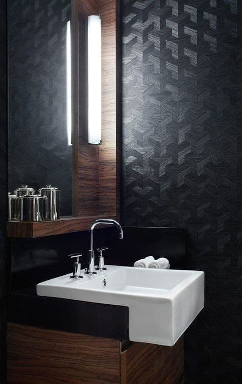 Contemporary black powder room with wall sconce and high ceiling.