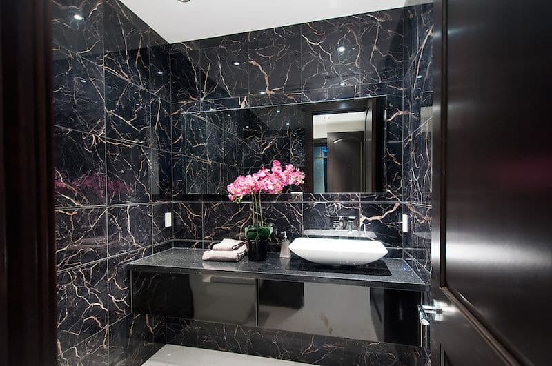 Black modern powder room with simple granite counters and vessel sink.