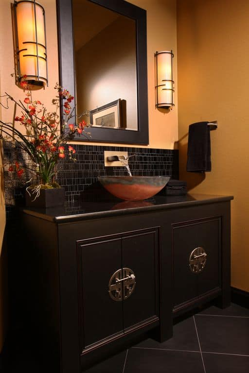 Black asian powder room with ceramic tile and wall sconce.